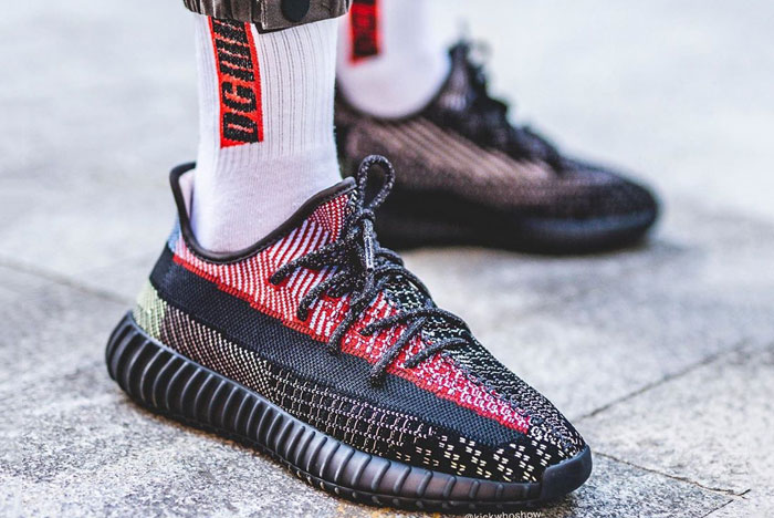 Person standing on sidewalk wearing black Yeezy 350 sneakers