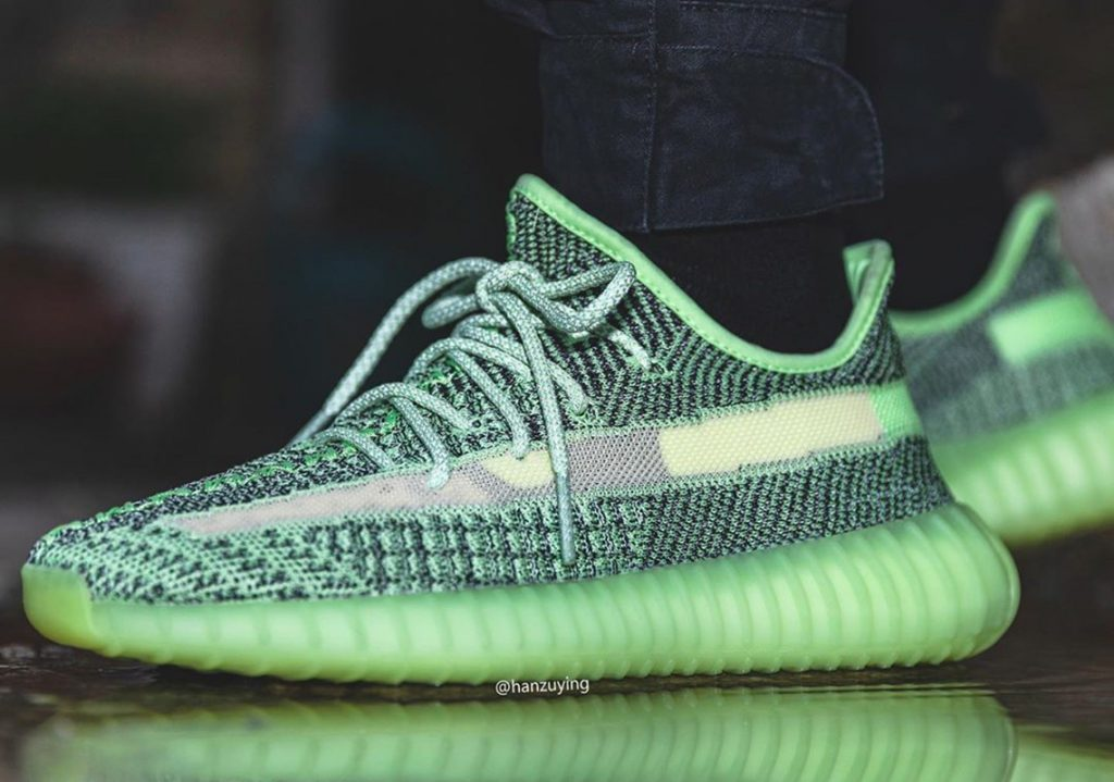 Person's feet wearing green Yeezreel sneakers